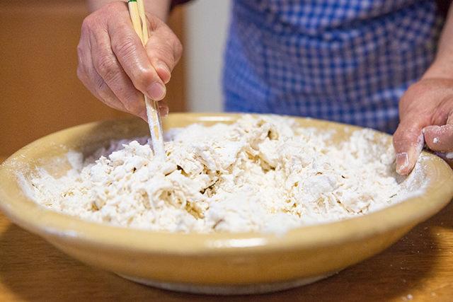 粉に水を加えて菜箸で混ぜている写真