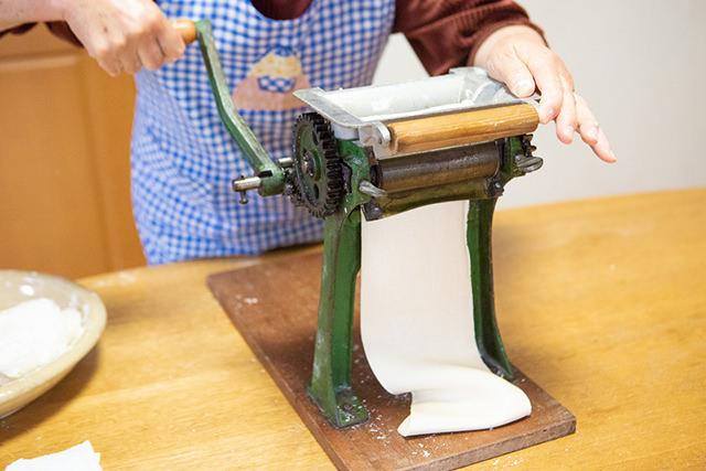 製麺機で生地を伸ばしている写真