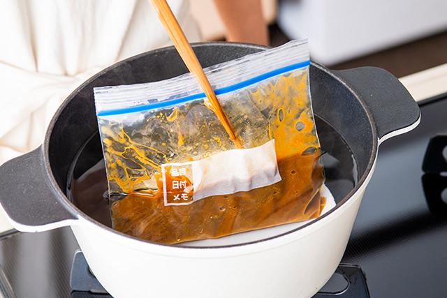 冷凍したカレーを菜箸でおさえている写真