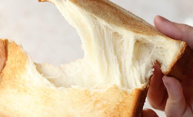 焼きあがった食パンを手で割っている写真