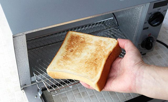 トースターから焼き上がった食パンを取り出す写真