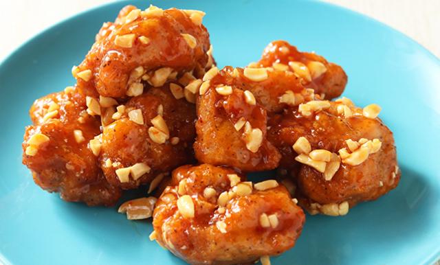 スイートチリソースが絡んだ唐揚げにピーナッツがまぶしてある写真