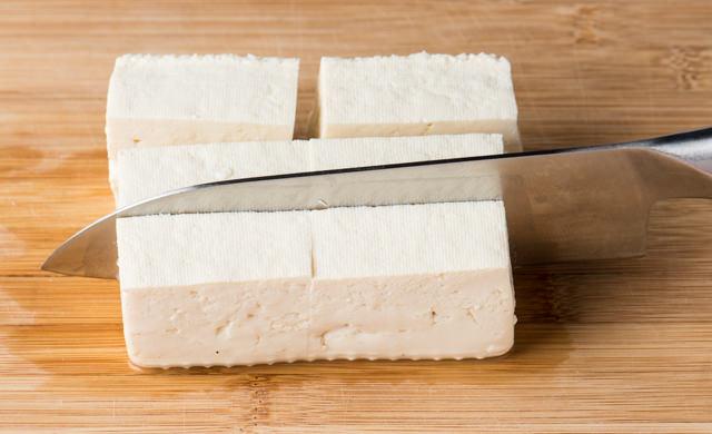 豆腐を包丁で2~3cmx4~5cmに切っている写真