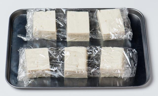 半丁ごとにラップに包んで並べた豆腐の写真
