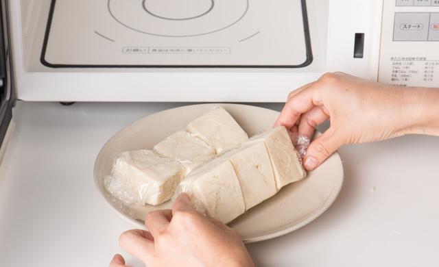 ラップで包んだ冷凍豆腐を電子レンジで解凍する写真