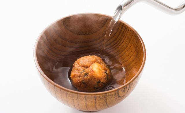 お椀に味噌玉を入れて熱湯を注ぐイメージの写真