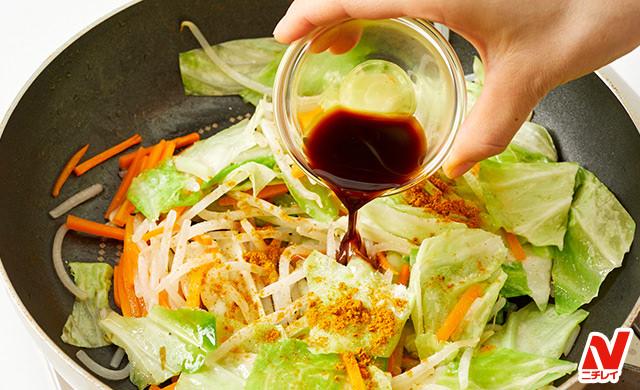 炒めた野菜に味付けをする写真