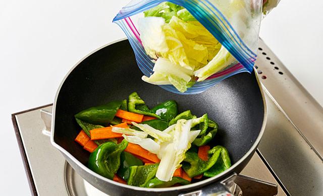 炒めものに冷凍白菜を加えている写真