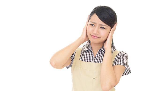 耳を押さえる女性の写真