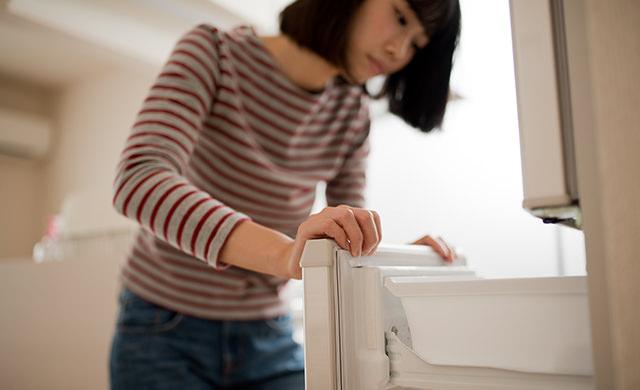 冷蔵庫のドアを開く女性の写真