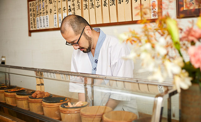 カウンターでおにぎりを握る三浦さんの写真