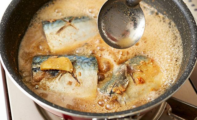 さばに煮汁をかける写真