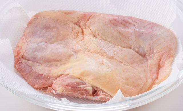 耐熱皿にペーパータオルを敷き、その上に鶏もも肉がのっている写真