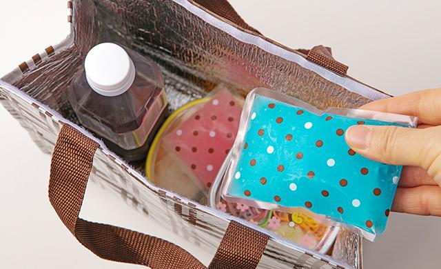 保冷バッグにそうめんそ入れた容器、トッピング具材を入れた容器、ペットボトルに入れて半冷凍にしためんつゆを入れたところに、保冷剤を入れようとしている写真
