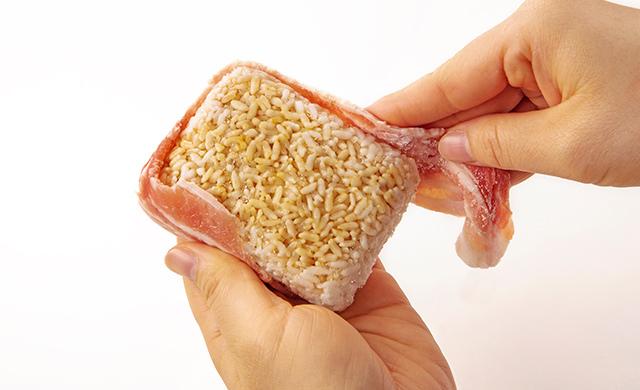 冷凍ごはんの側面に豚バラ薄切り肉を巻きつけている写真