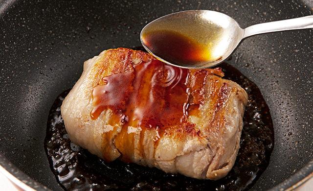 両面が焼けた肉巻きおにぎりに、スプーンで煮汁をかけている写真