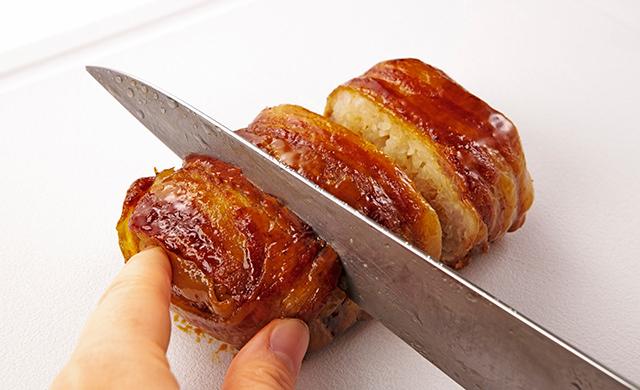 焼き上がった肉巻きおにぎりをまな板にのせ、包丁で食べやすく切っている写真