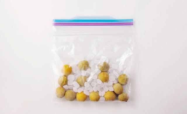保存袋に入れた冷凍梅と氷砂糖の写真
