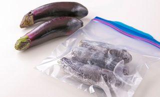 手前にラップに包んで冷凍用保存袋に入れた冷凍なす、奥に生のなすの写真