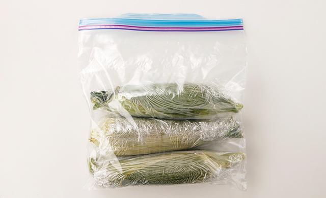 レンジ加熱した皮つきとうもろこしをラップで包み、冷凍用保存袋に入れた写真
