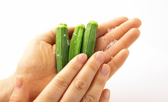 手のひらに塩をまぶし、手のひらをこすり合わせてオクラのうぶ毛を取り除いている写真