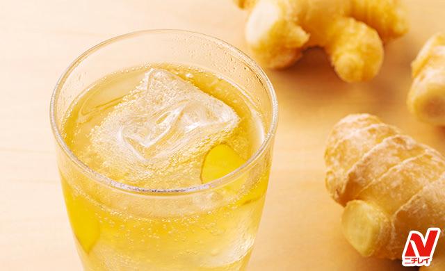 手前に氷を浮かべたグラスに入ったジンジャーエール、右と右奥に生姜の写真