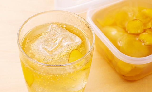 手前に氷を浮かべたグラスに入ったジンジャーエール、奥に保存容器に入ったジンジャーシロップの写真