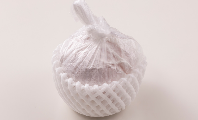 桃をペーパータオルで包んでポリ袋に入れ、フルーツキャップをつけた写真