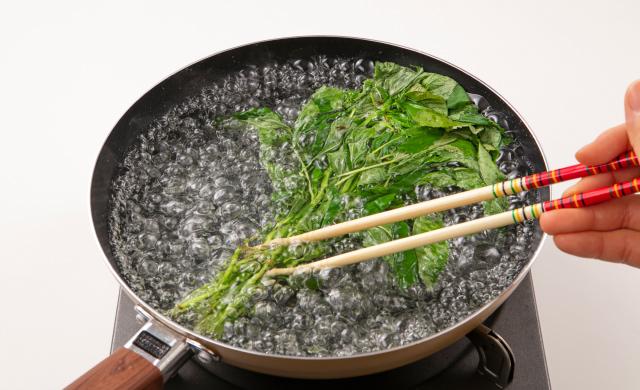 輪ゴムで束ねたモロヘイヤをフライパンに入れ、箸で押さえながらゆでている写真