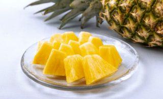 ひと口サイズに切ったパイナップルの皿盛りとパイナップル1個の写真