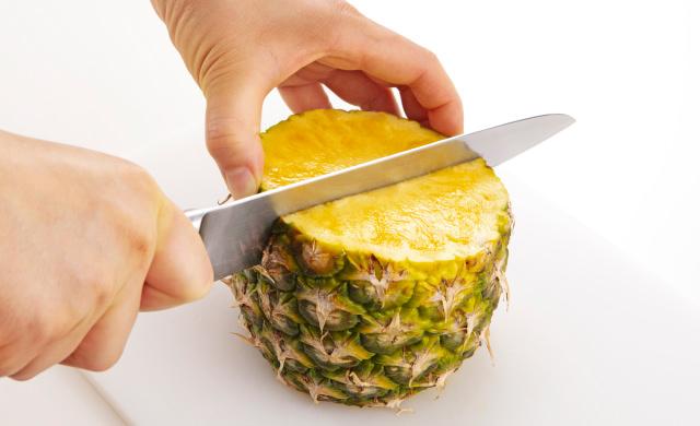パイナップルを立てて半分に切っている写真