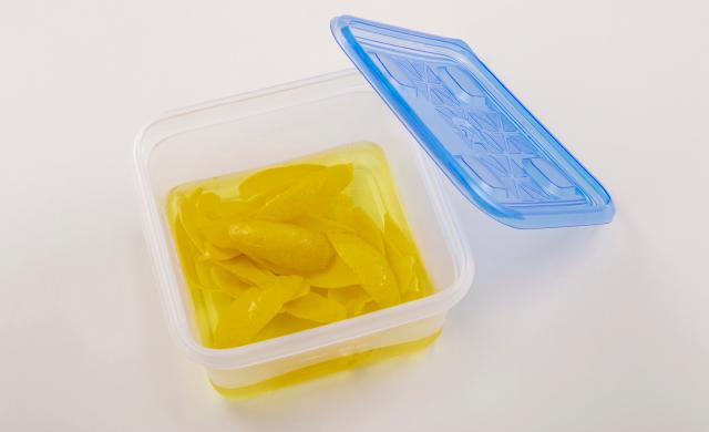レモンの皮を冷蔵用保存容器に入れて焼酎漬けにした写真