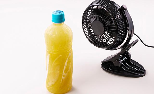 冷凍したペットボトル飲料に卓上扇風機を当てている写真
