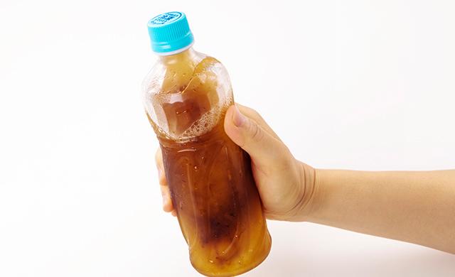 少し溶けた状態の冷凍ペットボトル飲料をシェイクしている写真