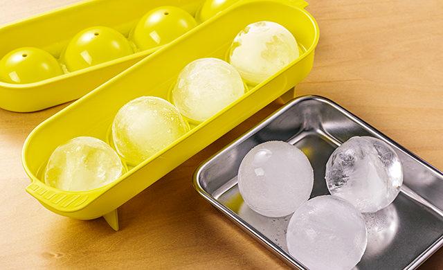 丸い製氷皿で作った丸い氷と金属バットに入った丸い氷の写真