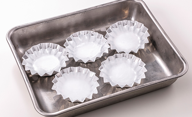 アルミカップを金属バットの上に並べて氷を作っている写真