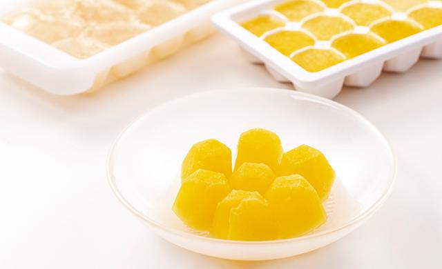 手前に皿に盛られたオレンジジュースの氷と、奥に製氷皿に入れて作ったオレンジジュースの氷と、麦茶の氷の写真