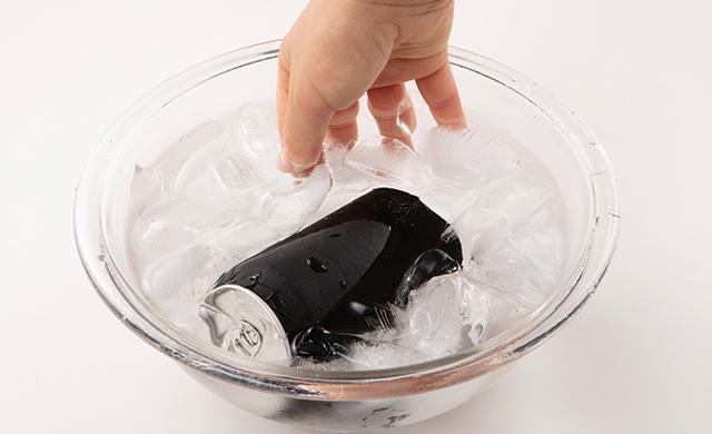 氷水を入れたボウルのなかで缶ジュースをかき混ぜている写真