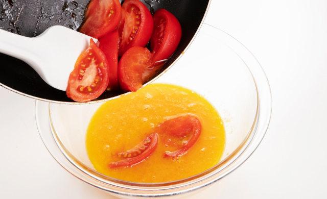 トマトを2の卵液に加えているところ