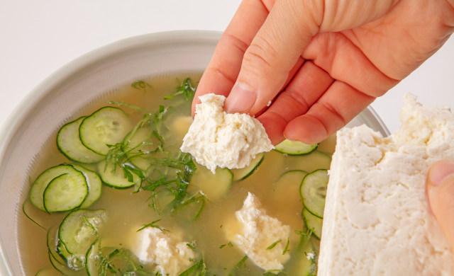 豆腐を指でちぎって冷や汁に入れている写真
