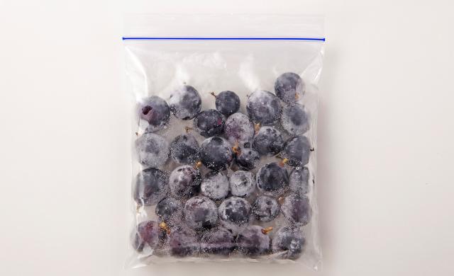 水けを拭き取ったぶどうの実を冷凍用保存袋に平らに入れた写真