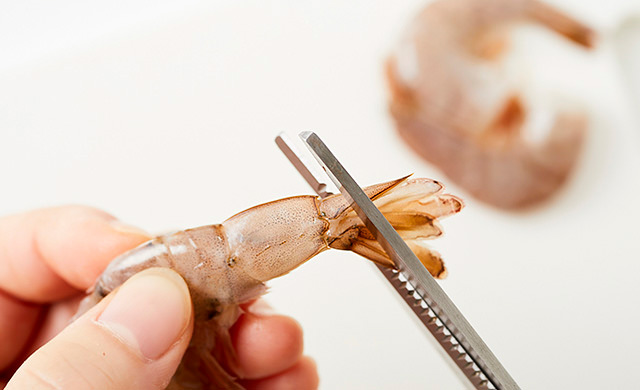 エビの尻尾をハサミでカットしている写真