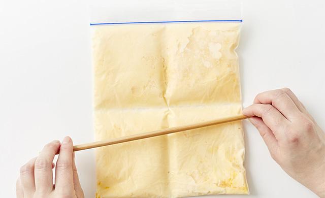 手作りアイスクリームが入った冷凍用保存袋に菜箸を当てて折れ目をつけている写真