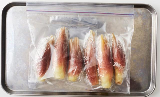 ラップで包んだみょうがを冷凍用保存袋に入れ、金属製バットにのせた写真