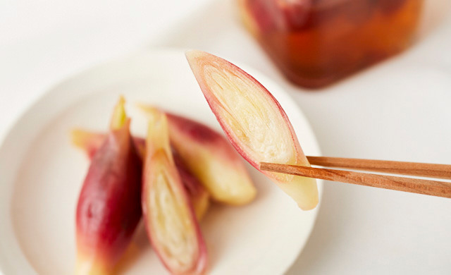 手前に甘酢漬けのみょうが、奥に瓶入りの甘酢漬けみょうが。甘酢漬けみょうがを箸で持ち上げている写真