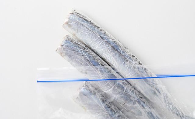 ラップに包まれて冷凍されたさんまを冷凍用保存袋から取り出している写真