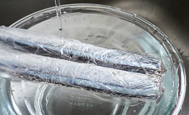 ラップに包まれて冷凍されたさんまをポリ袋に入れて流水解凍している写真