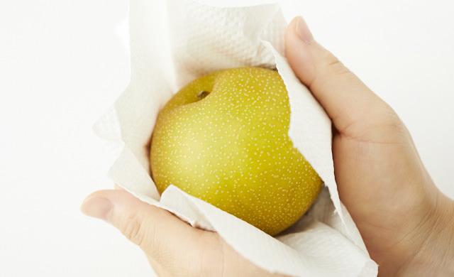 ペーパータオルで梨を包もうとしている写真