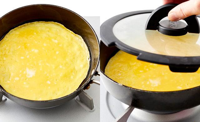 フライパンで焼いた卵液の縁が乾いて焼けている様子の写真/フライパンに卵液を入れて焼き、さらにふたをして蒸し焼きにしようとしている写真
