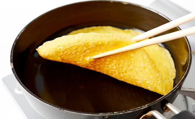フライパンで焼いた卵を菜箸を使って取り出している写真